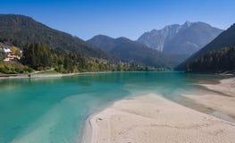 Vista dalla riva sabbiosa al villaggio Auronzo di Cadore il lago Santa Caterina e le dolomia delle montagne in Italia immagini stock