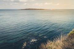 Vista dalla scogliera con erba asciutta al mare ed all'isola A Immagini Stock Libere da Diritti
