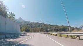 Vista dalla sinistra di giro dell'automobile su una strada principale sotto la cabina di funivia sui precedenti di belle montagne archivi video
