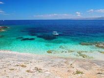 Vista dalla spiaggia di una barca sul mare Fotografia Stock
