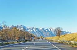 Vista dalla strada sulle montagne svizzere innevate Fotografia Stock