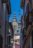 Vista dalle vie antiche della guglia di Toledo Cathedral e del Iglesia de fotografie stock