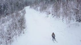 Vista das alturas ao esquiador que desce a inclinação do esqui vídeos de arquivo