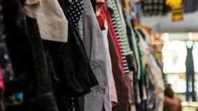 Vista das cremalheiras com roupa colorida das mulheres na loja filme