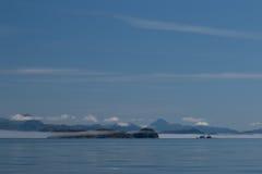 Vista das montanhas e de baixas nuvens brancas antes do céu azul e do mar calmo refletindo do ` s de Canadá dentro do corredor Imagens de Stock