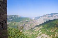 Vista das montanhas verdes céu azul, borda de uma parede de pedra Monastério Tatev, região de Syunik, Armênia Imagem de Stock