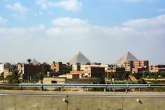 Vista das pirâmides de Keops, de Kefren e de Menkaure da estrada de anel do Cairo Adiante casas metade-construídas imagem de stock royalty free