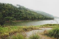 Vista das reservas de água para a represa hidroelétrico situada em Malásia Vegetação luxúria, montanha nevoenta nebulosa e parede imagem de stock