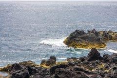 A vista das rochas da origem vulcânica e do oceano imagem de stock