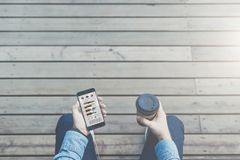 Vista de acima Vista dos olhos Close-up do smartphone com cartas, gráficos, diagramas, dados na tela e xícara de café Fotografia de Stock