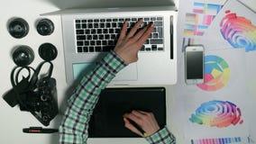 Vista de acima O homem é um fotógrafo que trabalha em sua tabuleta gráfica em um estúdio do projeto vídeos de arquivo