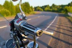 Vista de apertos de guiador da motocicleta no fundo da estrada secundária imagens de stock