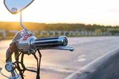 Vista de apertos de guiador da motocicleta no fundo da estrada secundária foto de stock