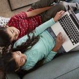 Vista de arriba de Brother And Sister Sitting en Sofa At Home Having Fun que juega en el ordenador portátil junto imagen de archivo