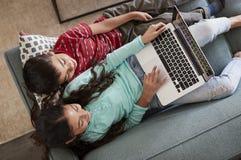 Vista de arriba de Brother And Sister Sitting en Sofa At Home Having Fun que juega en el ordenador portátil junto imagenes de archivo