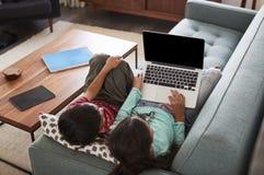 Vista de arriba de Brother And Sister Sitting en Sofa At Home Having Fun que juega en el ordenador portátil junto imagen de archivo libre de regalías