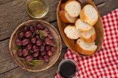 Vista de arriba de aceitunas y del pan en placa en la tabla Fotografía de archivo libre de regalías