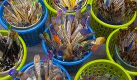 Vista de arriba de docenas de brochas viejas en envases Imagen de archivo libre de regalías