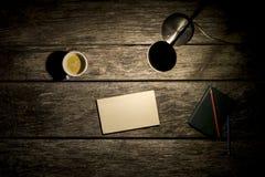 Vista de arriba de la lámpara de escritorio, del café, del cuaderno y del pedazo en blanco de Foto de archivo