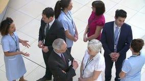 Vista de arriba de la reunión del personal hospitalario en la recepción ocupada metrajes