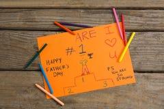 Vista de arriba de la tarjeta y de los creyones de felicitación del día de padres en la tabla Fotografía de archivo