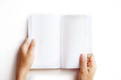 Vista de arriba de las manos que sostienen un libro en blanco Fotos de archivo libres de regalías