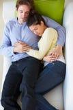 Vista de arriba de los pares que se relajan en el sofá fotos de archivo