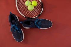 Vista de arriba de los zapatos azules de los deportes por la estafa y las bolas de tenis Imagen de archivo libre de regalías