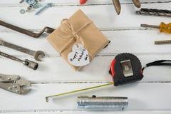Vista de arriba del regalo del día de padres con las herramientas de la carpintería Imagen de archivo libre de regalías
