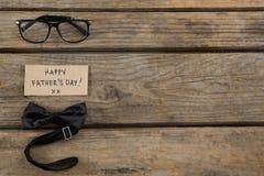Vista de arriba del texto feliz del día de padres con las lentes y la corbata de lazo Imagen de archivo