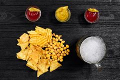 Vista de arriba del vidrio y de los bocados de cerveza con la salsa en la tabla de madera negra Foto de archivo