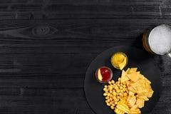 Vista de arriba del vidrio y de los bocados de cerveza con la salsa en la tabla de madera negra Foto de archivo libre de regalías