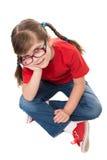 Vista de arriba hacia abajo de un sittinf elegante de la niña en el piso Foto de archivo libre de regalías