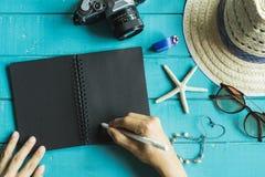Vista de arriba de los accesorios y de los artículos del ` s del viajero con el cuaderno Foto de archivo