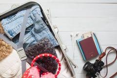 Vista de arriba de los artículos del ` s del viajero, ropa en maleta del equipaje Foto de archivo libre de regalías