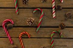 Vista de arriba de los bastones de caramelo y de los conos del pino en la tabla Foto de archivo