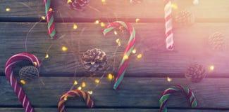 Vista de arriba de los bastones de caramelo y de los conos del pino en la tabla Imágenes de archivo libres de regalías