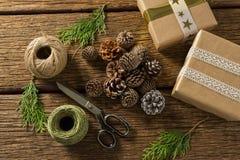 Vista de arriba de los conos del pino con las cajas de regalo y los carretes del hilo Foto de archivo libre de regalías