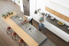 Vista de arriba de pares ocupados en cocina moderna Fotos de archivo