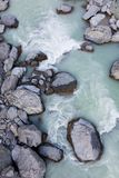 Vista de arriba de rocas y de la corriente alpinas con agua glacial, Nueva Zelanda foto de archivo