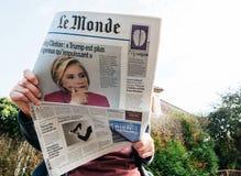 Vista de baixo da mulher que lê o jornal o mais atrasado Le Monde com o retrato de Hillary Clinton Foto de Stock Royalty Free