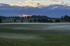 Vista de campos y de prados verdes de niebla en la puesta del sol Fotografía de archivo libre de regalías