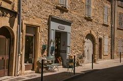 Vista de casas e de lojas de pedra típicas em uma rua de Lourmarin foto de stock royalty free