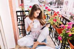 Vista de cima da menina bonita no pijama que come o café da manhã no balcão na manhã na cidade Guarda um copo, lendo sobre imagens de stock royalty free