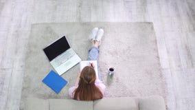 Vista de cima da menina do estudante que senta-se na escrita do tapete no caderno video estoque