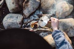 A vista de cima da menina do viajante derrama pr?pria o caf? quente nas montanhas pr?ximo ? fogueira foto de stock royalty free