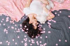 Vista de cima da mulher bonita no pijama que refrigera com pouco cão na cama com cobertura cor-de-rosa Apreciar em casa relaxa no imagem de stock
