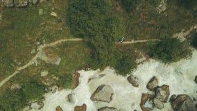 Vista de cima do turista da montanha que anda ao longo do rio rápido Caminhando a montanha filme