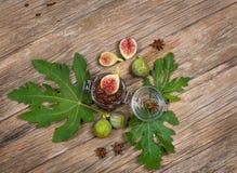 Vista de cima dos figos na folha e no doce de figo na tabela de madeira Imagens de Stock Royalty Free