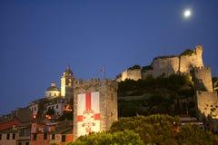 Vista de construções do ` s de Portovenere na noite sob a lua com um castelo, uma torre e uma catedral iluminados Imagens de Stock Royalty Free
